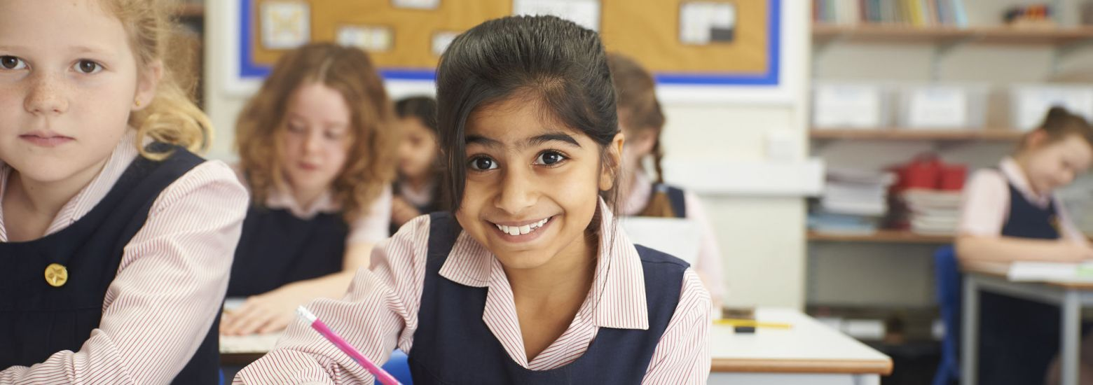smiling school girl writing with a pencil